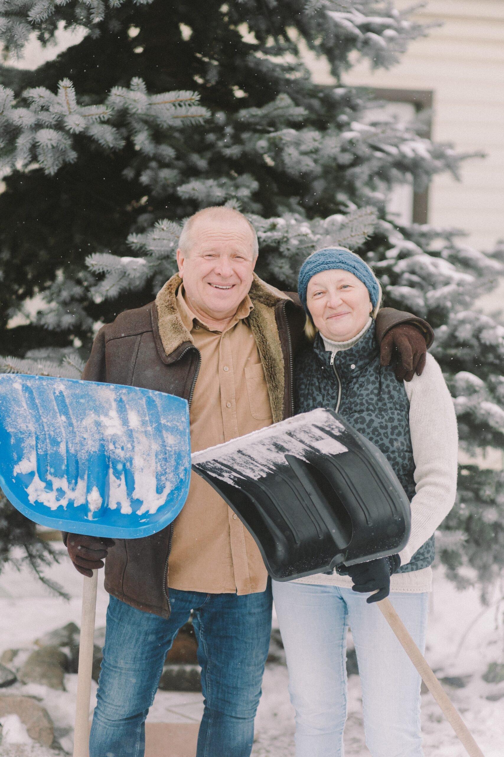 senior couple shovelling snow outside their home