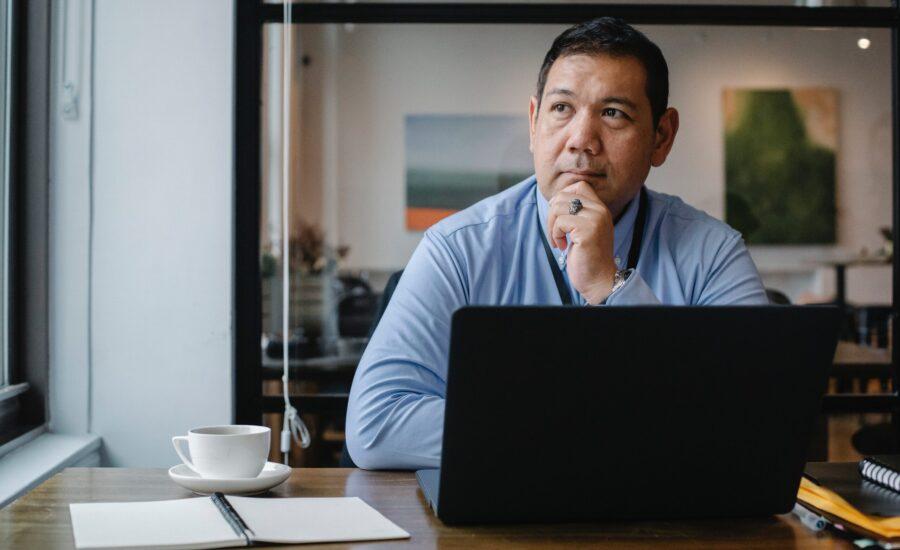 man sitting at laptop looking pensive