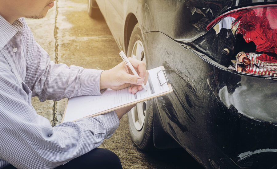 An adjustor knelt and taking notes based on the damage of the rear lights of a car.