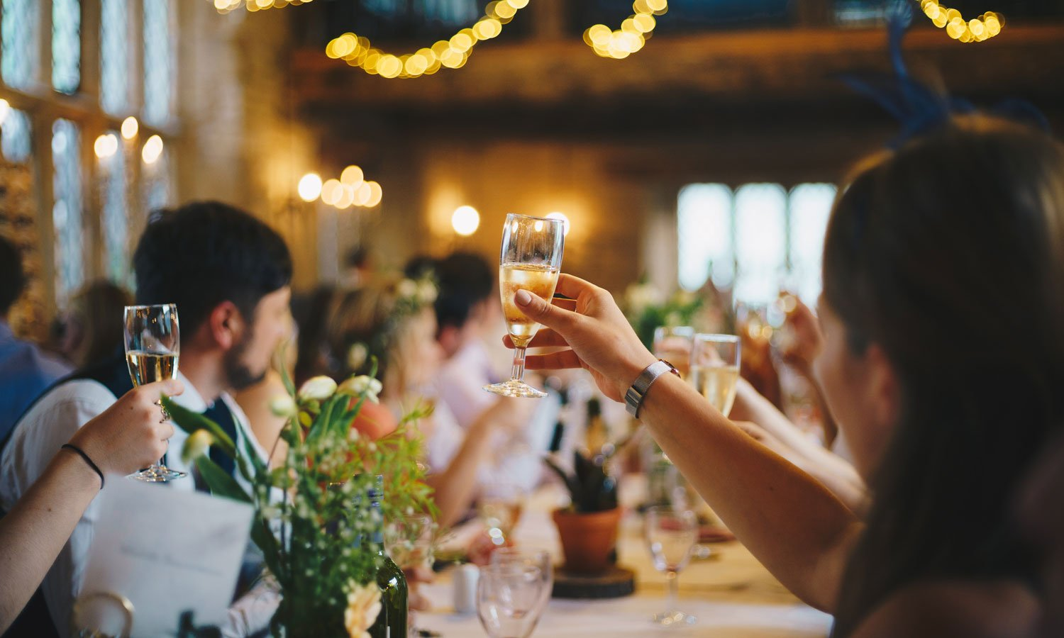 A long table of wedding guests with a glass of champagne raised to toast the couple