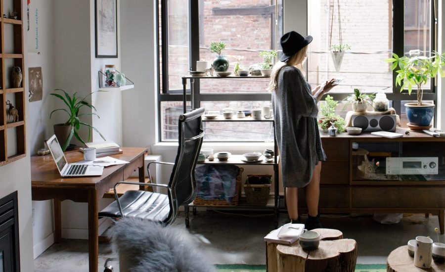 woman standing by window in her home office
