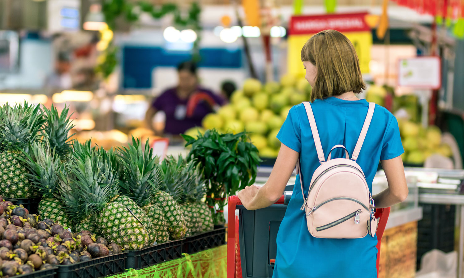 A woman in the fruit section of the grocery aisle in front of a stand of pineapples