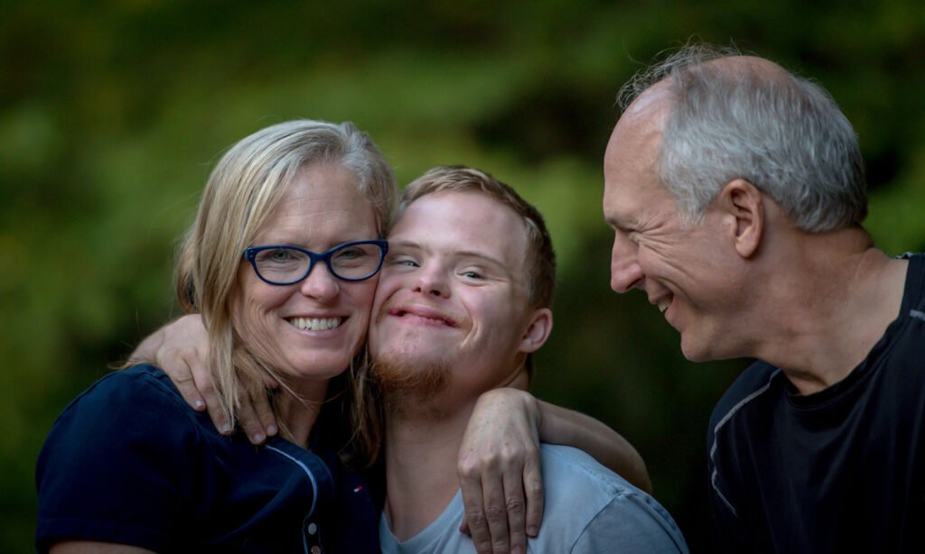 An older couple with their young adult son, who has down syndrome.