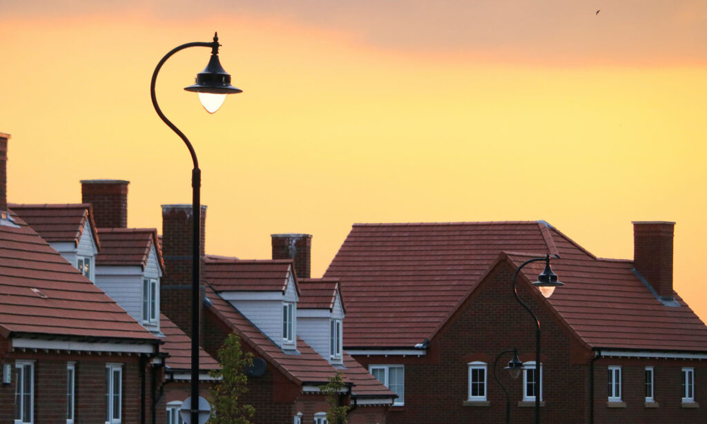 The sun is setting on a row of houses on a suburban street.