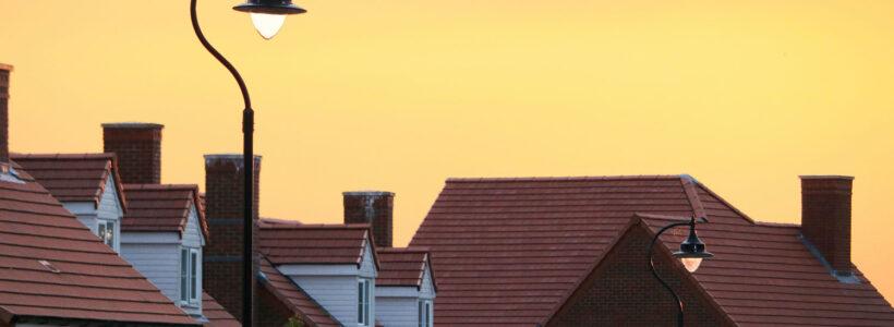 The sun is setting on a row of houses on a suburban street.