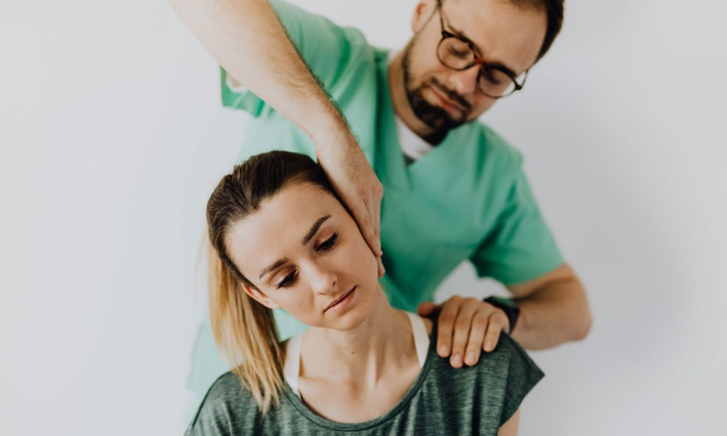 A woman having her neck treated by a rehabilitation specialist.