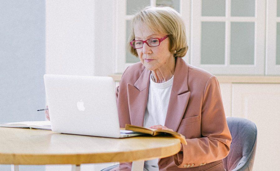 senior woman using laptop computer at table