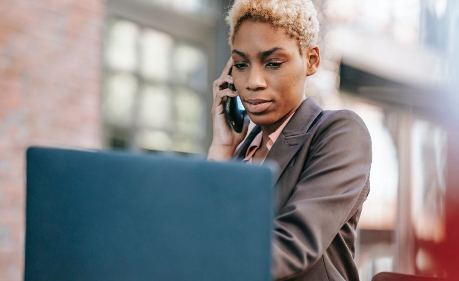 concerned woman speaking on cellphone and looking at laptop