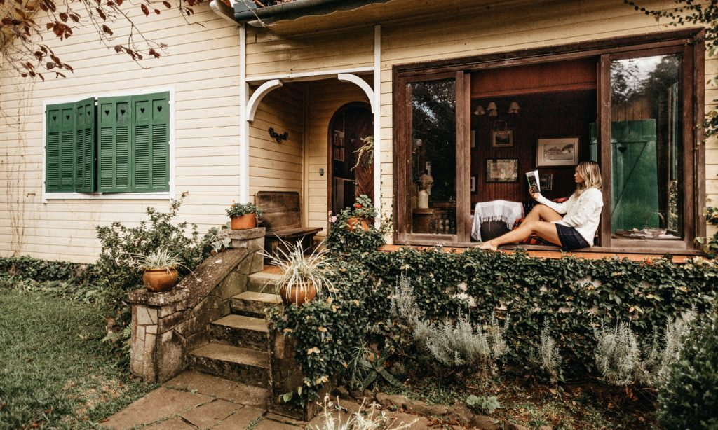 A woman reading in the window of her new home–happy as can be.