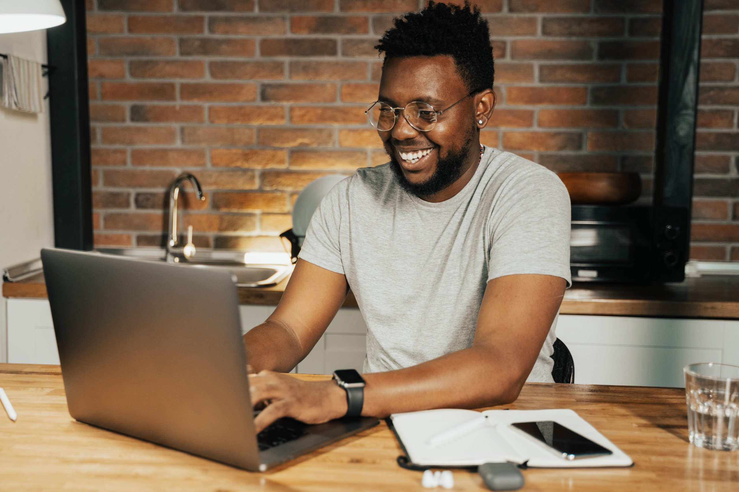 smiling man using laptop computer in his home