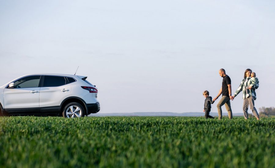 Young family with kids travelling by car, stopped in the field