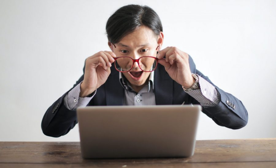 Man with glasses looking surprised at computer monitor