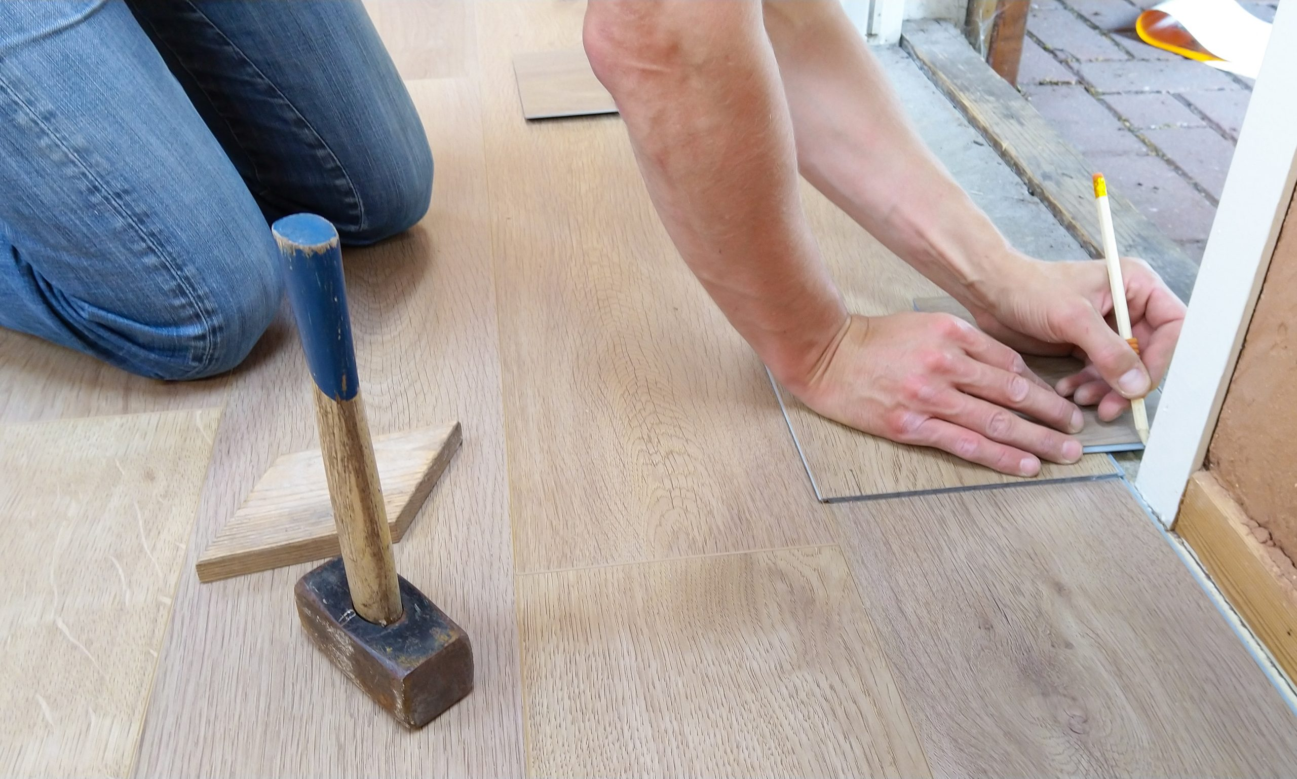 person installing flooring inside a home