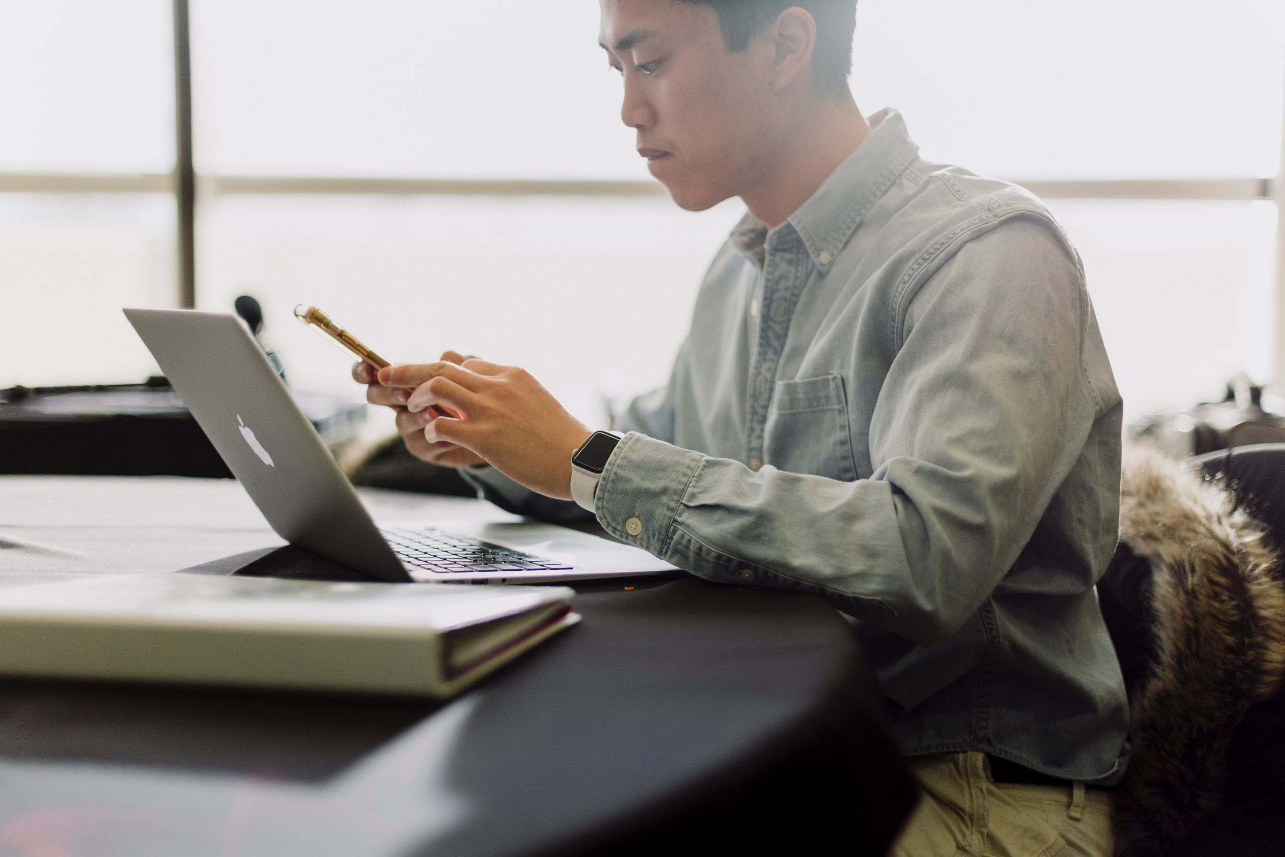 man looking concerned while reading on mobile phone and laptop
