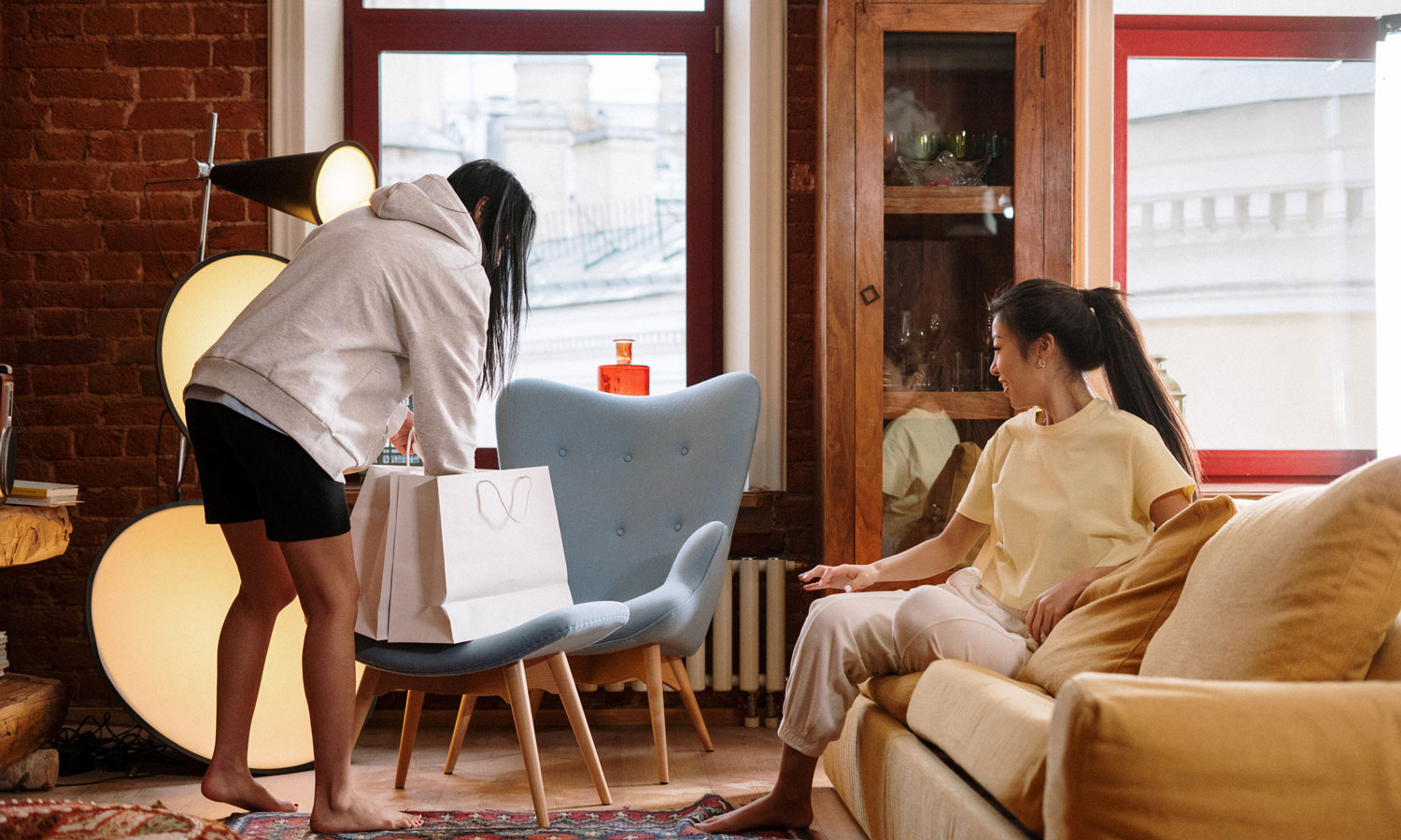 Two women in their home, as one shows the other the things she bought that day. She's reaching in the shopping bag.