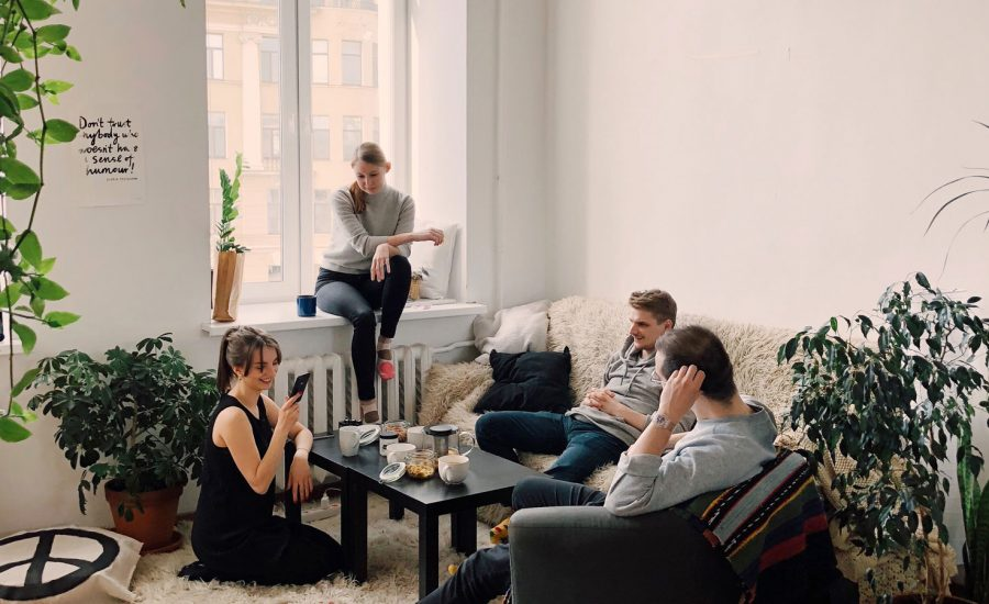 A group of friends are sitting around the living room of an apartment