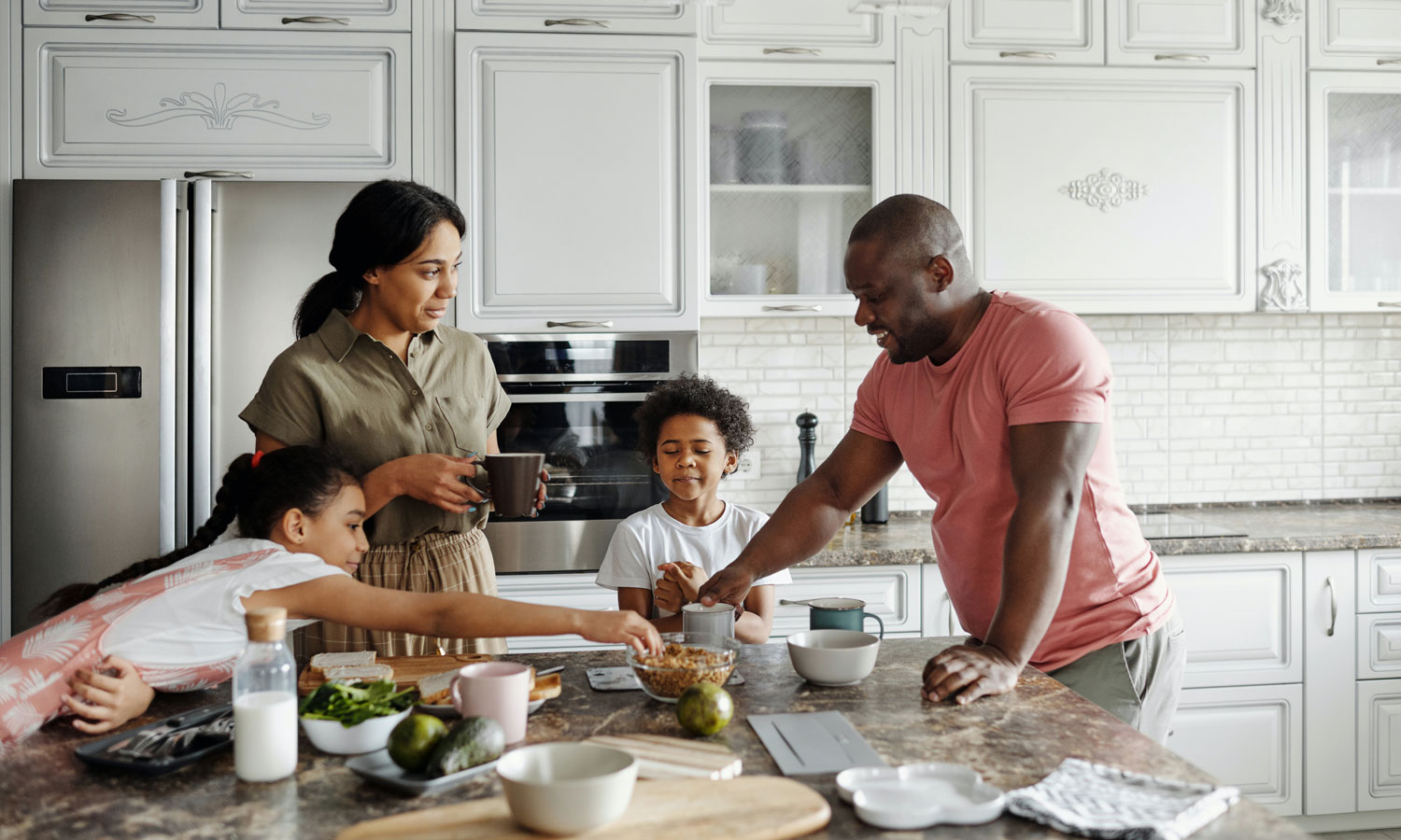 Family eating granola together in their top-of-the-line kitchen