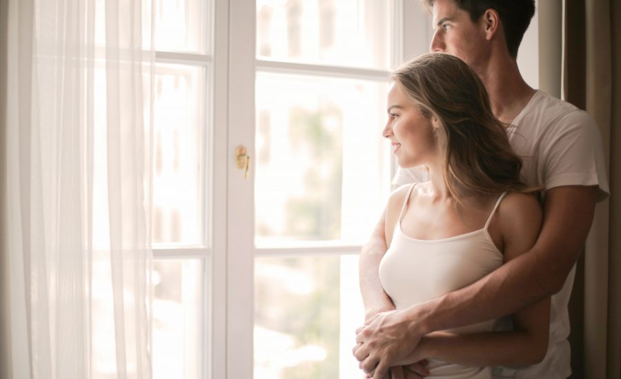 young couple looks out window of their home