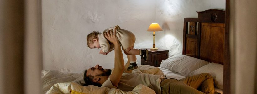 A father and a baby playing together on a bed at the cottage.