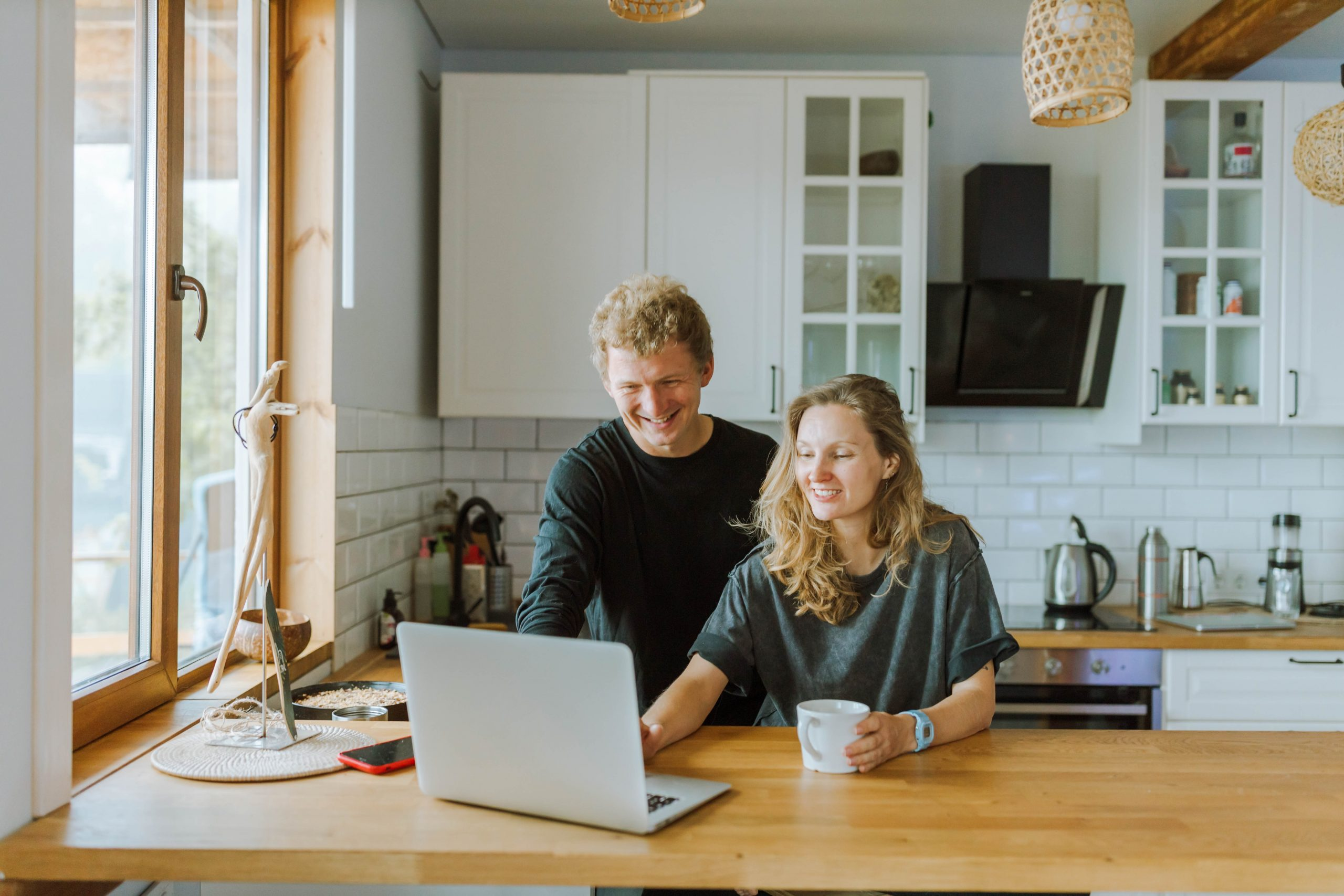 couple consulting laptop computer in their kitchen