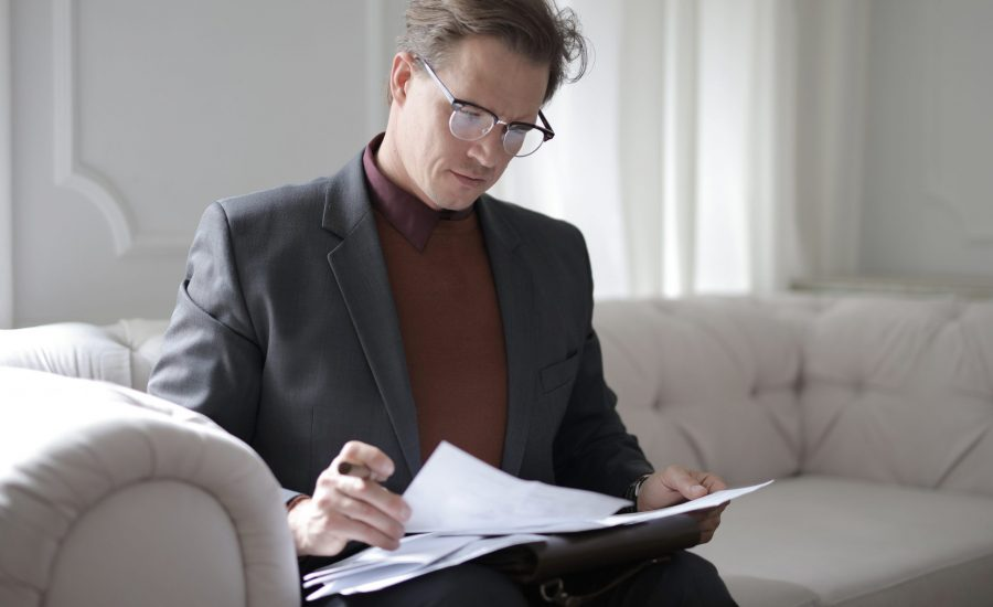 man sitting on couch reading paperwork
