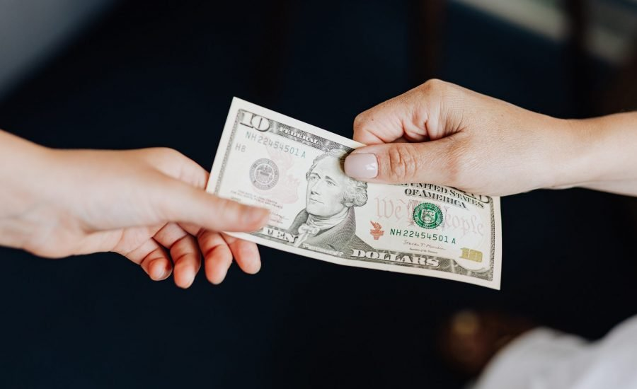 one hand passing $10US to another