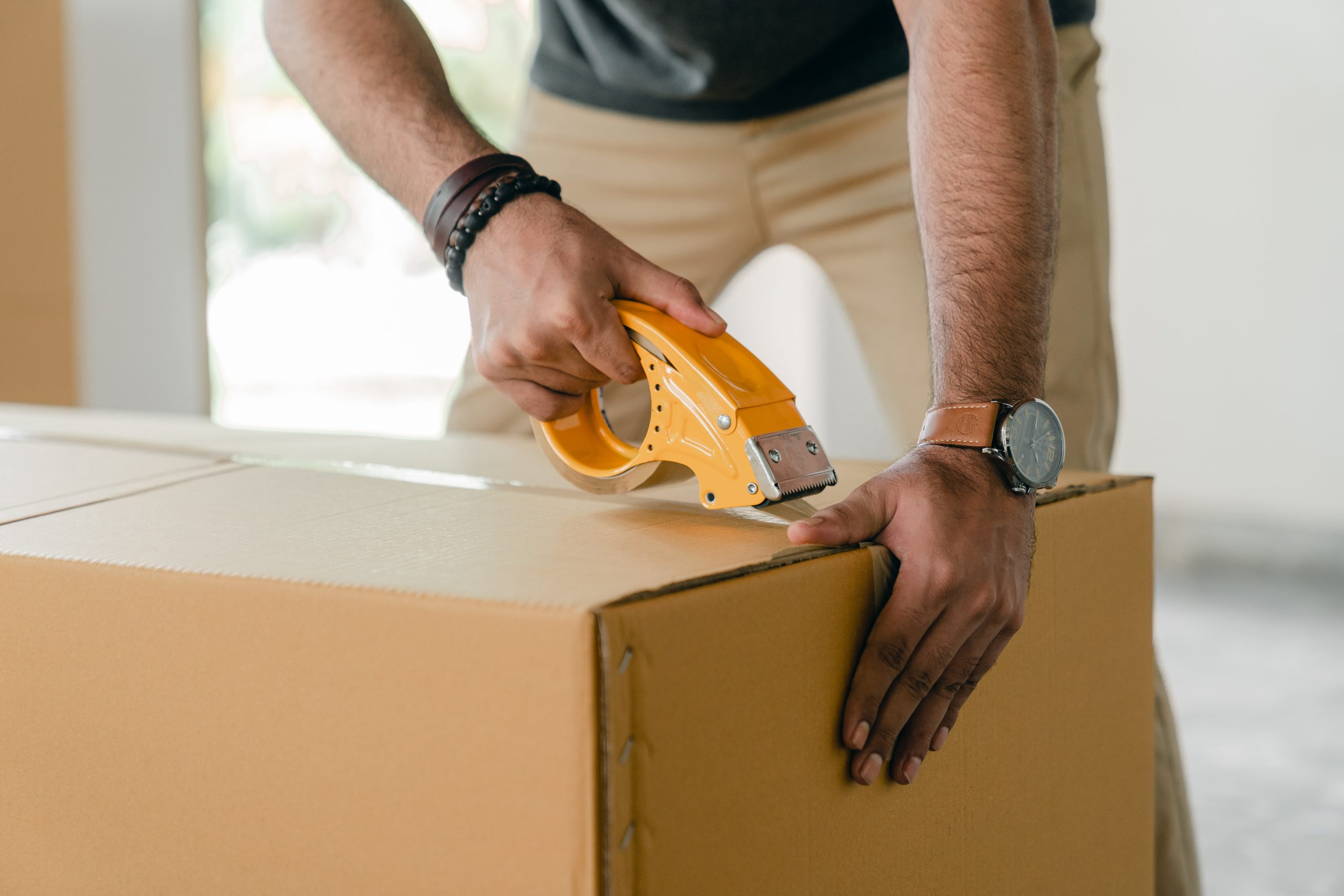 man taping a moving box closed
