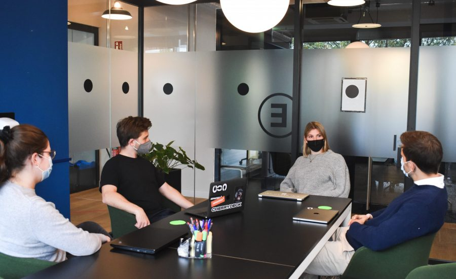 masked colleagues meet in coworking space