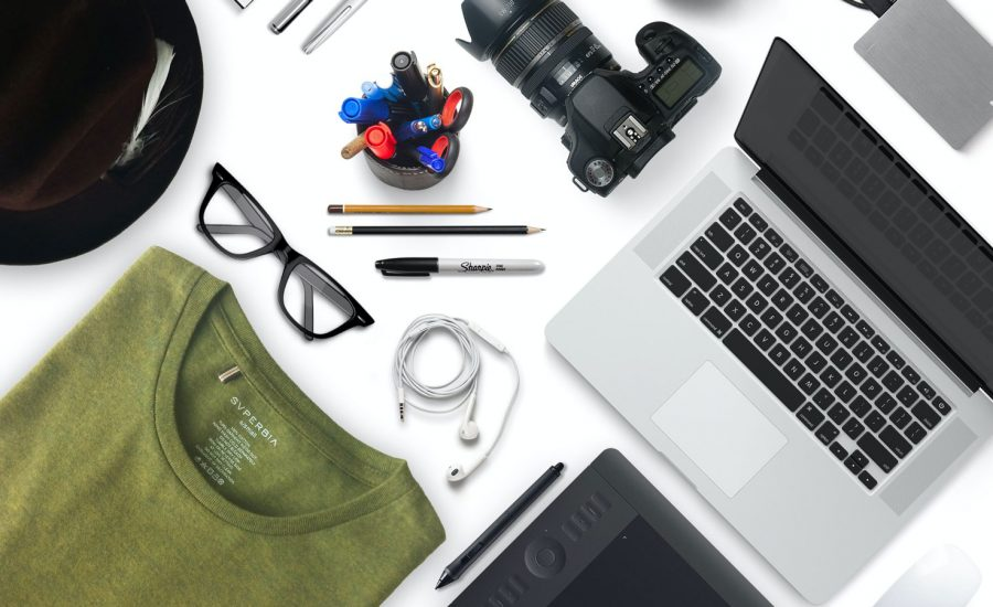 A flat lay of items you may own, including a tablet, computer, camera, phone, glasses and more.