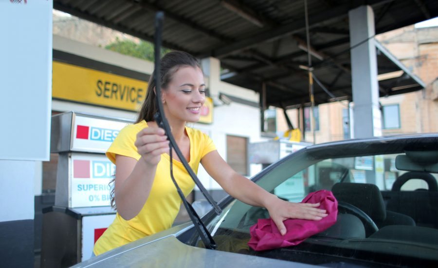 A woman washes the rear window of her car after getting gas. She has a big smile. Very happy.