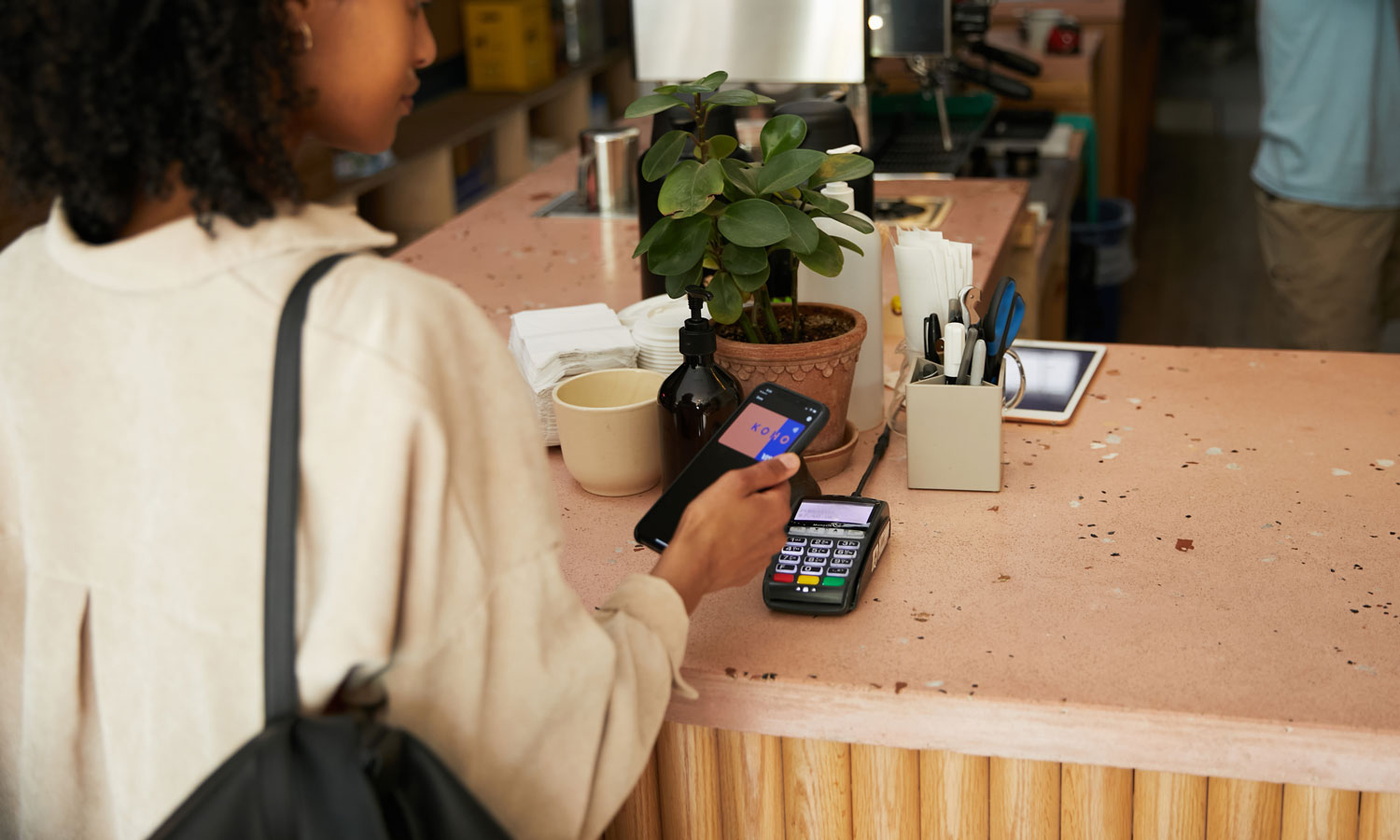 A woman is buying a coffee at an artisanal café, using her KOHO credit card.