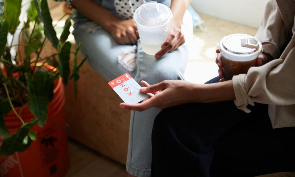 A friend is explaining how she uses her KOHO card to a friend.