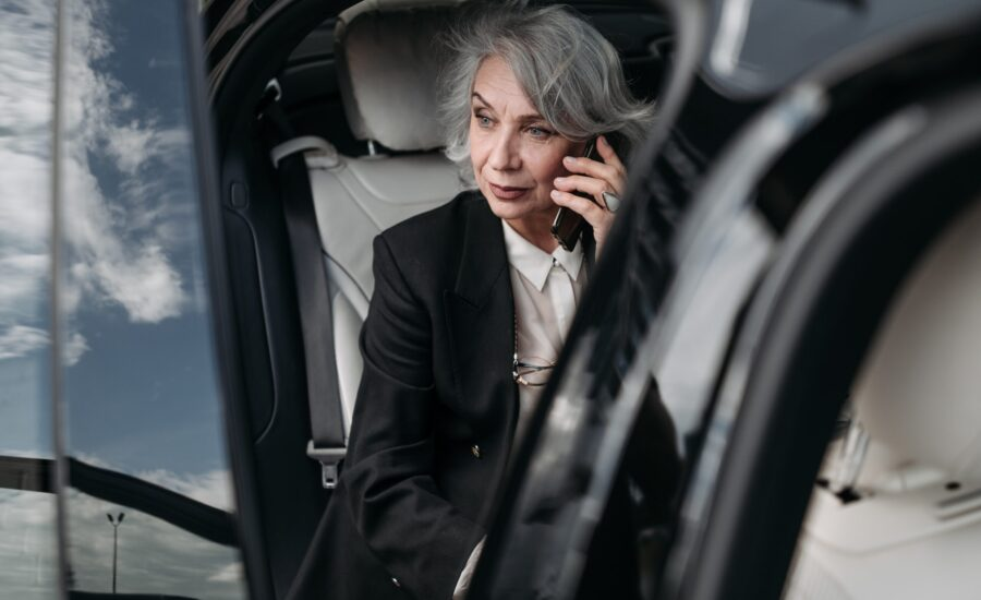 grey-haired woman listening to mobile phone in car