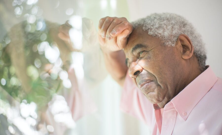 older man resting head against window
