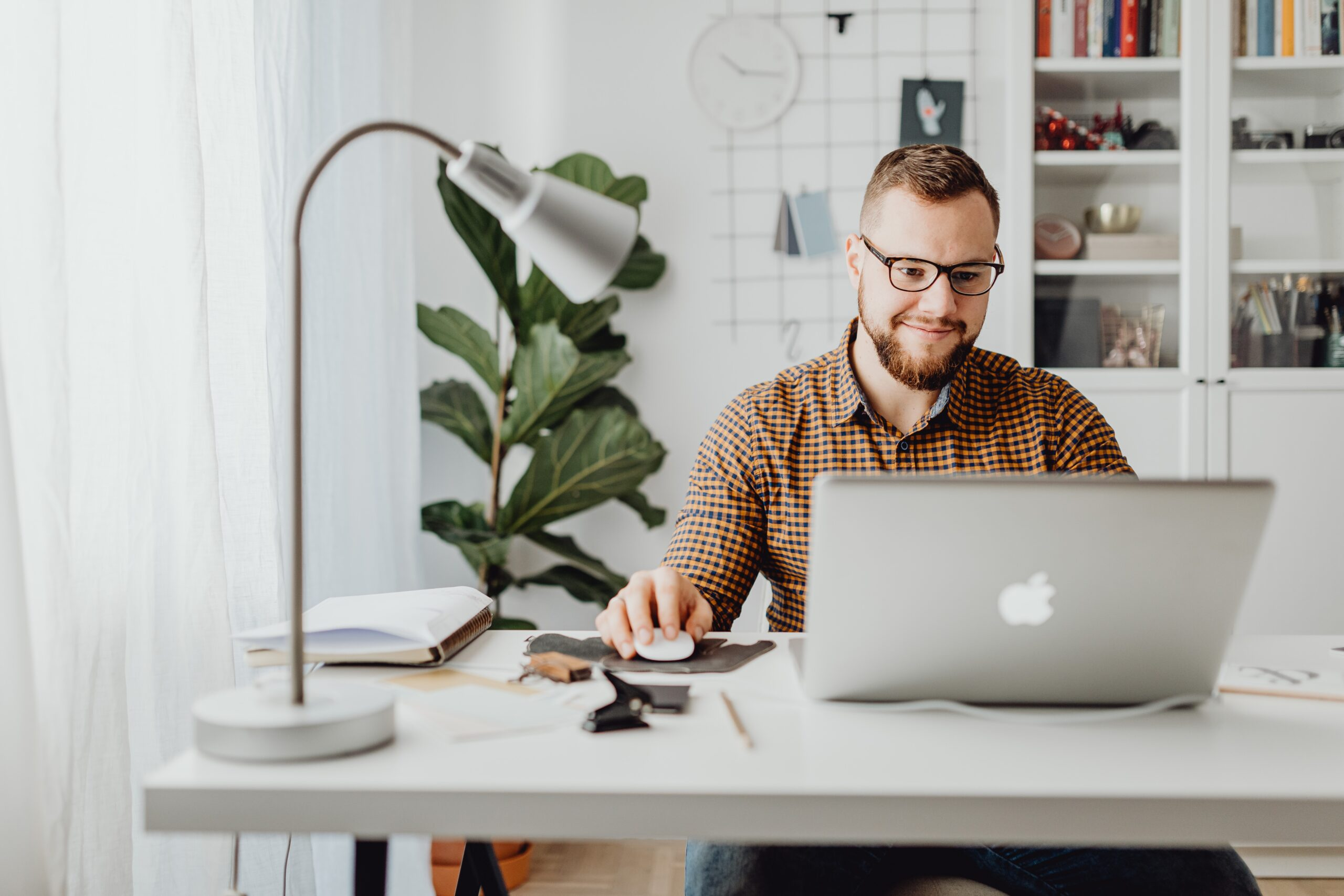 man with glasses sitting at desk and reading laptop computer screen