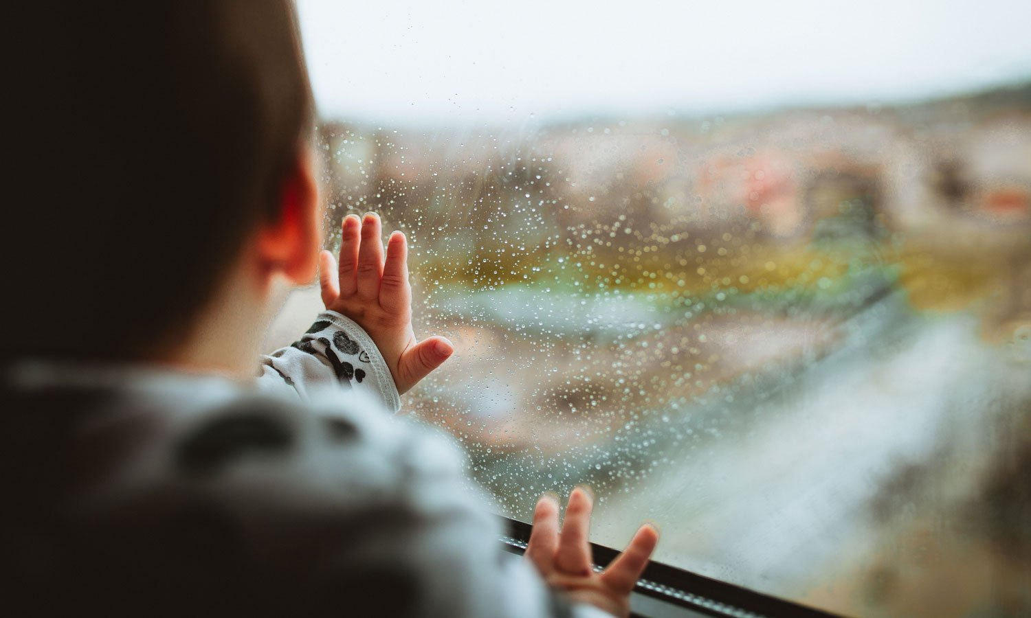 A baby touching a rain-drenched window.