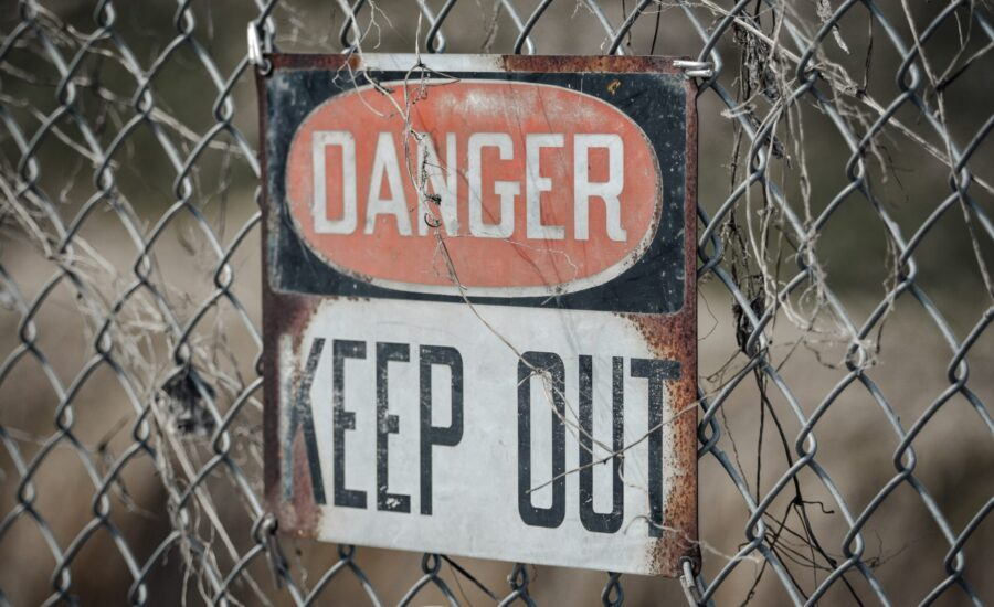 danger sign on chain-link fence