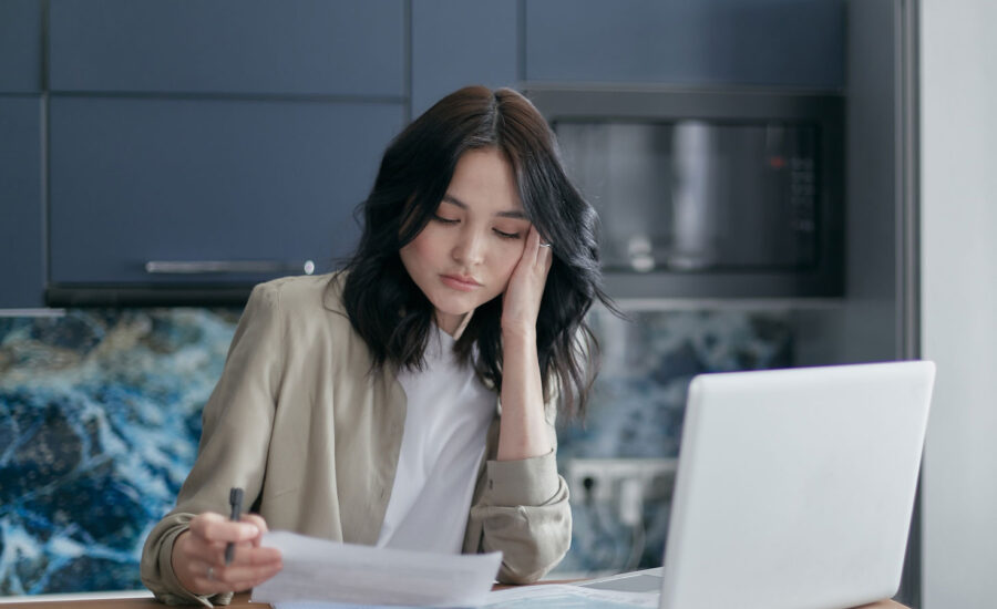 A woman at her computer, reading her bills.