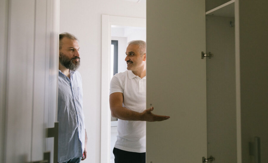 Two men looking around an empty room that's ready to be moved into.