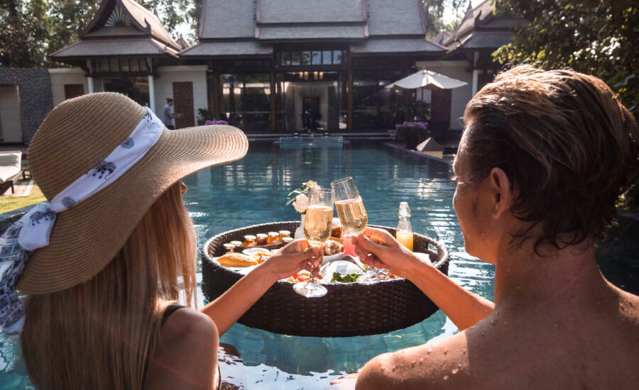 a couple by the resort pool clinking glasses of champagne during a vacation they've ben waiting for.