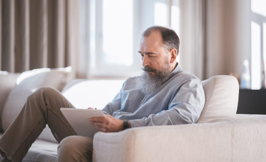 grey-haired man studying on couch