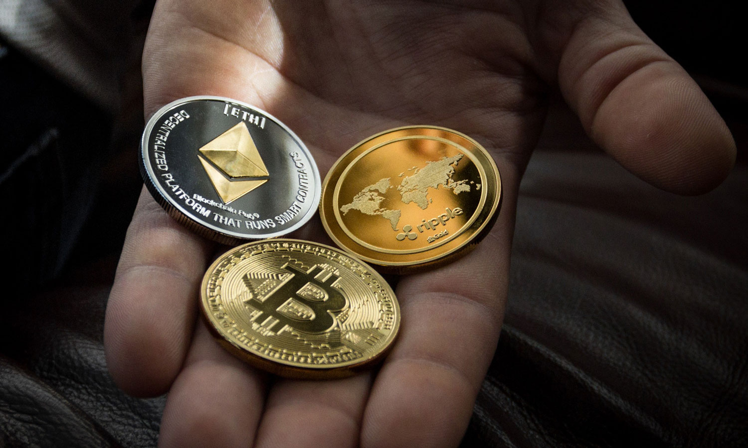 A hand holding coins with digital currencies on the faces