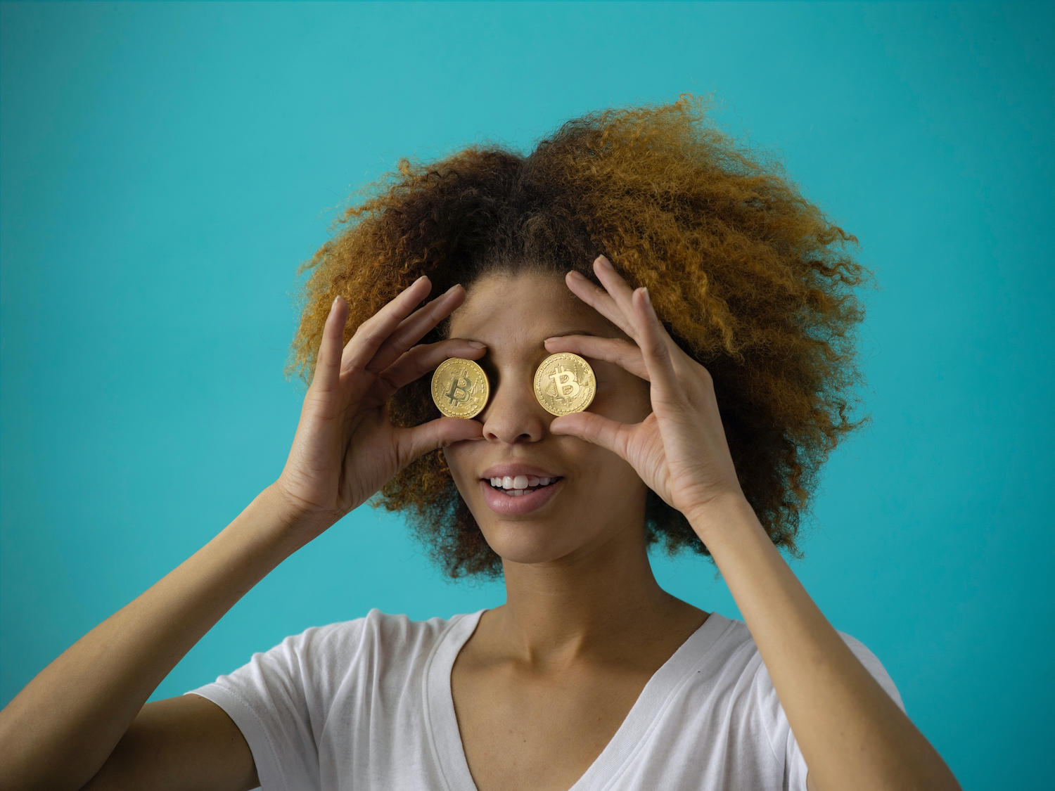 A woman is seen holding two coins to her eyes